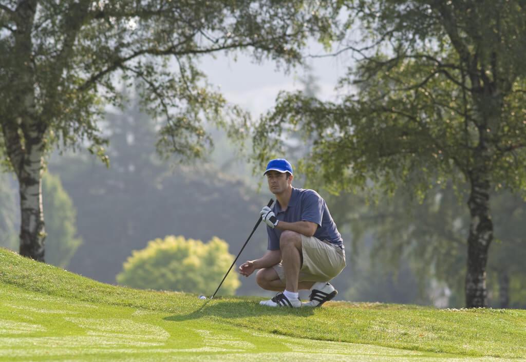 Hockender Golfer am Golfplatz vor Wald